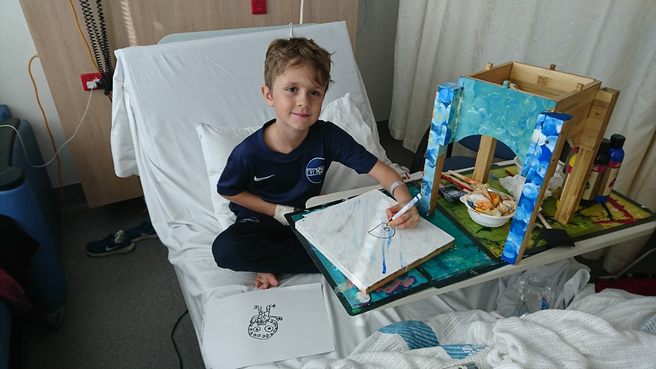 Boy painting in hospital bed